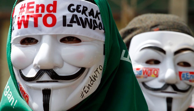 Indonesian activists wear masks while protesting against the World Trade Organization meeting in Bali, Indonesia on Tuesday (3/12). Indonesia is hosting the World Trade Organization Ministerial Conference from Dec. 3 - 6. AP/Firdia Lisnawati