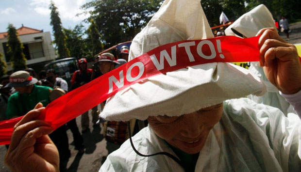 A protester from South Korea's Korean Women Peasant Association (KWPA) ties a banner to her headdress as she gets ready to take to the streets ahead of the ninth World Trade Organization (WTO) Ministerial Conference in Denpasar, on the Indonesian resort island of Bali (3/12). REUTERS/Edgar Su