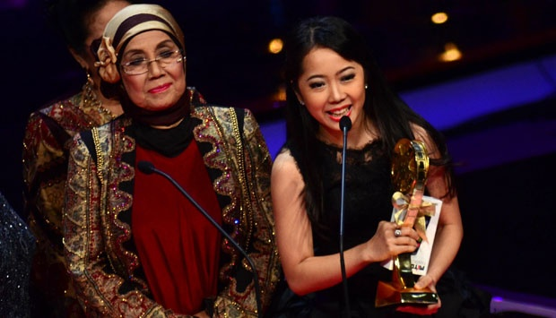 Aktris Karina Salim mengangkat piala usai meraih penghargaan pendatang baru wanita terbaik dalam perannya di film `Why They Don't Talk About, When They Talk About Love` pada malam penganugrahan Indonesian Movie Awards 2014 di Studio 8 RCTI, Jakarta, (14/5) malma. TEMPO/Nurdiansah