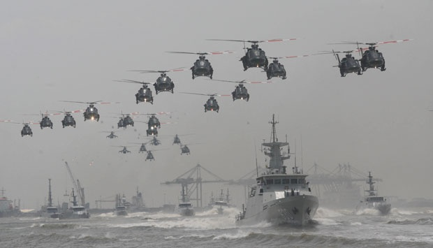 Indonesian Air Force helicopters fly in formation over the fleet of military ships in a show of force during a ceremony commemorating the 69th anniversary of Indonesian Armed Forces in Surabaya, East Java, Indonesia (10/7). AP/Trisnadi