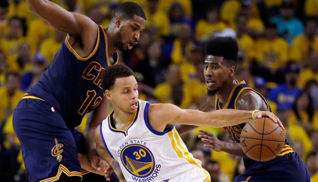 Guard Golden State Warriors Stephen Curry (30) berusaha melewati dua pemain Cleveland Cavaliers Tristan Thompson (13) dan Iman Shumpert pada game kedua Final NBA di Oakland, 8 Juni 2015. AP/Ben Margot