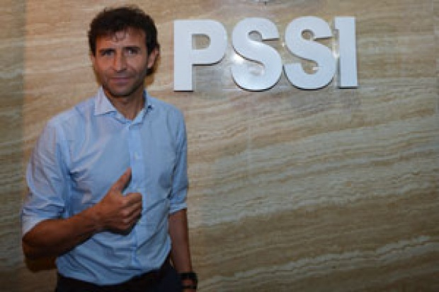 Luis Milla in front of PSSI logo.