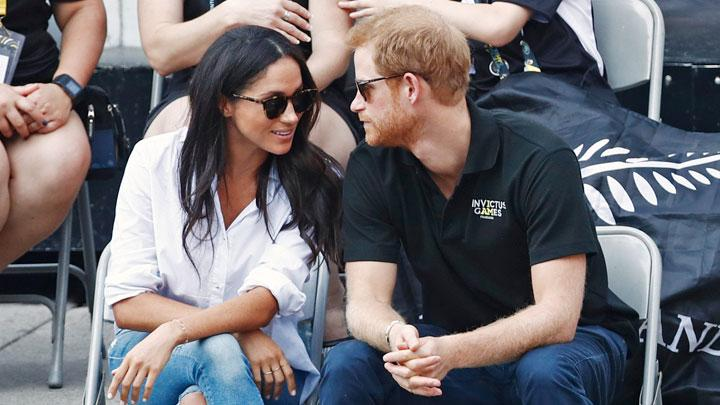Pangeran Harry berbicara dengan kekasihnya  Meghan Markle saat menyaksikan pertandingan tenis kursi roda dalam acara Invictus Games di Toronto, Ontario, Kanada, 25 September 2017. REUTERS/Mark Blinch