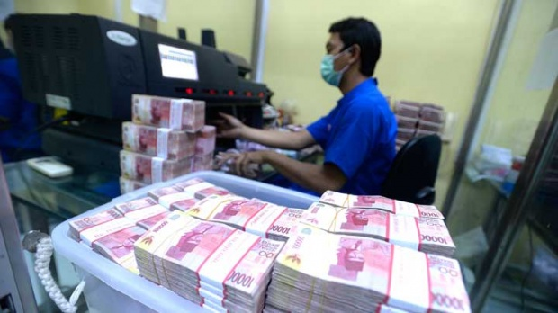 Bank employees count Indonesian rupiah bank notes in cash center Bank BNI headquarter's, Jakarta, November 21, 2017. Tempo/Tony Hartawan