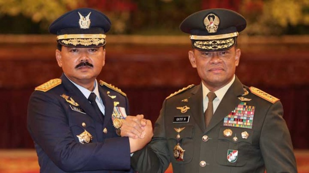 Indonesia's new Armed Forces Chief Marshall Hadi Tjahjanto, left, and his predecessor Gen. Gatot Nurmantyo pose for photographers during his inauguration ceremony at the presidential palace in Jakarta, Dec. 8, 2017. AP