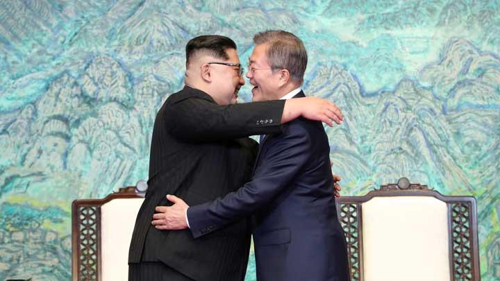 Presiden Korea Selatan, Moon Jae-in, memeluk pemimpin Korea Utara, Kim Jong Un, usai penandatangan kesepakatan di Rumah Perdamaian di desa Panmunjom di zona gencatan senjata, 27 April 2018.  (Korea Summit Press Pool via AP)