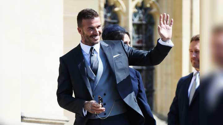 Mantan bintang Manchester United, David Beckham, melambaikan tangan saat tiba dalam acara pernikahan Pangeran Harry dan Meghan Markle di kapel St George di Istana Windsor, 19 Mei 2018.  David Beckham juga menghadiri pernikahan Pangeran William dan Kate Middleton. (Chris Jackson/pool photo via AP)