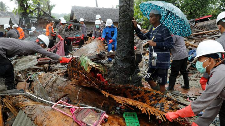 A man holding an umbrella watches as personnel search through the debris of his damaged house after a tsunami, in Sumur, Banten province, Indonesia December 26, 2018. A state of emergency has been declared until Jan. 4, which authorities hope will make it easier to deploy assistance, said Sutopo Purwo Nugroho, spokesman for the national disaster mitigation agency. REUTERS/Jorge Silva