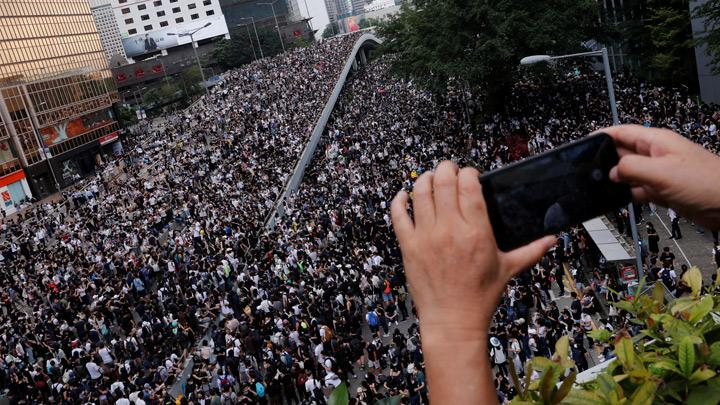 A person uses a mobile phone to record a protest against a proposed extradition bill in Hong Kong, China June 12, 2019. Tens of thousands of Hong Kong demonstrators surrounded the Chinese-ruled city's legislature on Wednesday, forcing it to postpone a second round of debate on an extradition bill that would allow people to be sent to mainland China for trial. REUTERS/Tyrone Siu