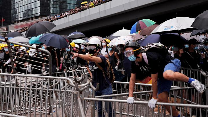 A protester mounts a metal barricade during a demonstration against a proposed extradition bill in Hong Kong, China June 12, 2019.