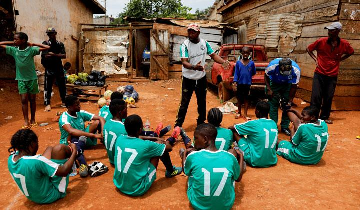 Emmanuel Eteme Biolo, a girls' U17 team coach, talks with his team during half-time of the match at the Rail Foot Academy field in Yaounde, Cameroon, May 4, 2019. The academy currently trains around 70 girls, most of whom come from poor backgrounds and would otherwise not be able to afford even their own soccer boots, said Biolo. REUTERS/Zohra Bensemra