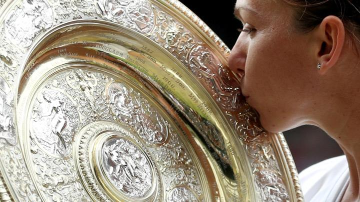 Romania's Simona Halep kisses the trophy as she celebrates after winning the final against Serena Williams of the U.S. in Wimbledon at All England Lawn Tennis and Croquet Club, London, Britain, July 13, 2019. Simona Halep became the first Romanian to win a Wimbledon singles title after she beat seven-times champion Serena Williams 6-2 6-2 in the final on Saturday. REUTERS/Hannah McKay