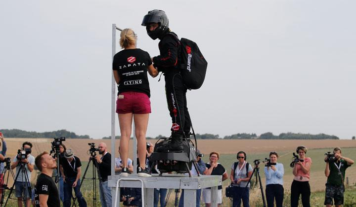 French inventor Franky Zapata is seen on a Flyboard next to his wife after landing during a demonstration as he prepares to cross the English channel from Sangatte in France to Dover, at the Saint-Inglevert aerodrome near Calais, France, July 24, 2019. The 36 minute flight was widely acclaimed as a significant achievement, with the company Bleriot set up becoming a major manufacturer of aircraft. REUTERS/Pascal Rossignol