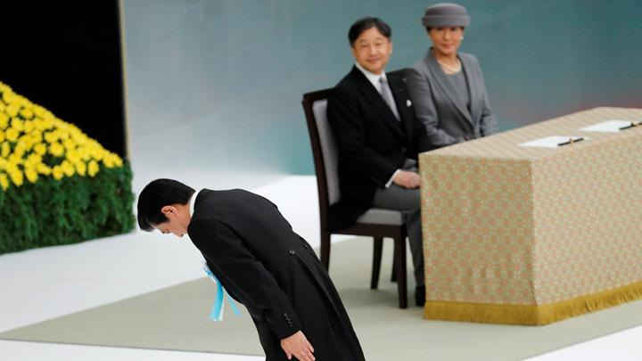 Japan's Prime Minister Shinzo Abe bows at a memorial service ceremony marking the the 74th anniversary of Japan's surrender in World War Two, while Japan's Emperor Naruhito and Empress Masako watch, in Tokyo, Japan August 15, 2019. Japan's new emperor, Naruhito, expressed deep remorse over the country's wartime past and prayed for global peace on Thursday, echoing his father's words in remarks at an annual ceremony marking Tokyo's surrender in World War Two. REUTERS/Kim Kyung-Hoon
