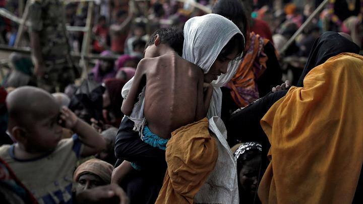 A woman carries her ill child in a refugee camp at Cox's Bazar, Bangladesh, September 26, 2017. This month marks the second anniversary of the fleeing of more than 730,000 Rohingya from Myanmar's northwest Rakhine State to Bangladesh after a military-led crackdown in response to an attack by Muslim militants on Myanmar police posts. REUTERS/Cathal McNaughton/File Photo