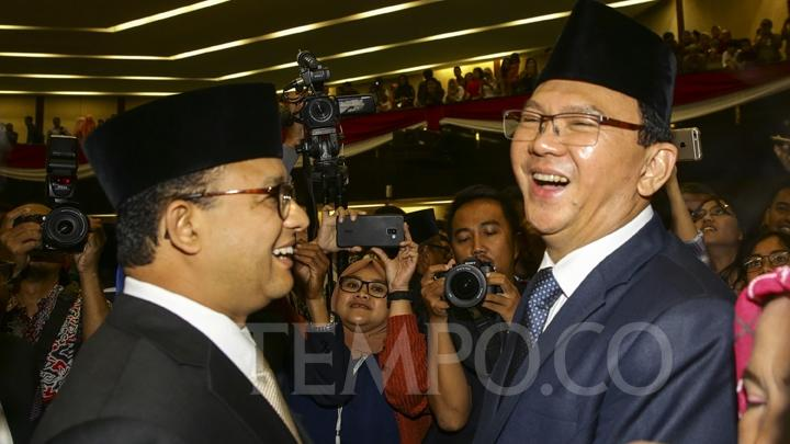 Jakarta Governor Anies Baswedan shares a laugh with his predecessor, Basuki Tjahaja Purnama or Ahok after attending the inauguration of Jakarta councilors at the Jakarta Regional Legislative Council (DPRD DKI Jakarta) building, Monday, August 26, 2019. TEMPO/Muhammad Hidayat