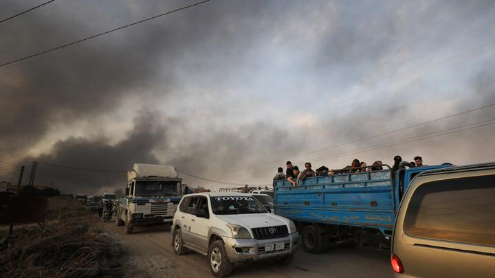People stand at a back of a truck as they flee Ras al Ain town, Syria October 9, 2019. Turkey launched a military operation against Kurdish fighters in northeast Syria on Wednesday just days after U.S. troops pulled back from the area, with air strikes and artillery hitting YPG militia positions around the border town of Ras al Ain. REUTERS/Rodi Said