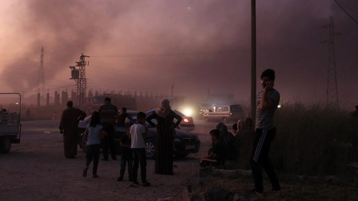 People stand together as they flee Ras al Ain town, Syria October 9, 2019. Turkey had been poised to enter northeast Syria since U.S. troops, who have been fighting with Kurdish-led forces against Islamic State, started to leave in an abrupt policy shift by U.S. President Donald Trump. The withdrawal was criticised in Washington as a betrayal of America's Kurdish allies. REUTERS/Rodi Said