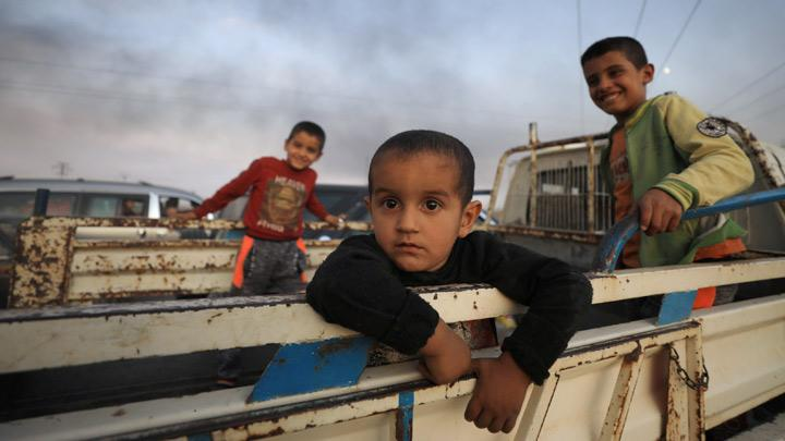 Boys stand at a back of a truck as they flee Ras al Ain town, Syria October 9, 2019. Turkish howitzers also started hitting bases and ammunition depots of the Kurdish YPG militia. The artillery strikes, which also targeted YPG gun and sniper positions, were aimed at sites far from residential areas. REUTERS/Rodi Said