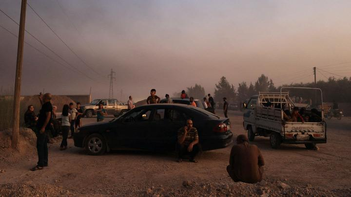 People stand together as they flee Ras al Ain town, Syria October 9, 2019. Large explosions also rocked Ras al Ain, just across the border across from the Turkish town of Ceylanpinar, a CNN Turk reporter said. The sound of planes could he heard above and smoke was rising from buildings in Ras al Ain, he said. REUTERS/Rodi Said