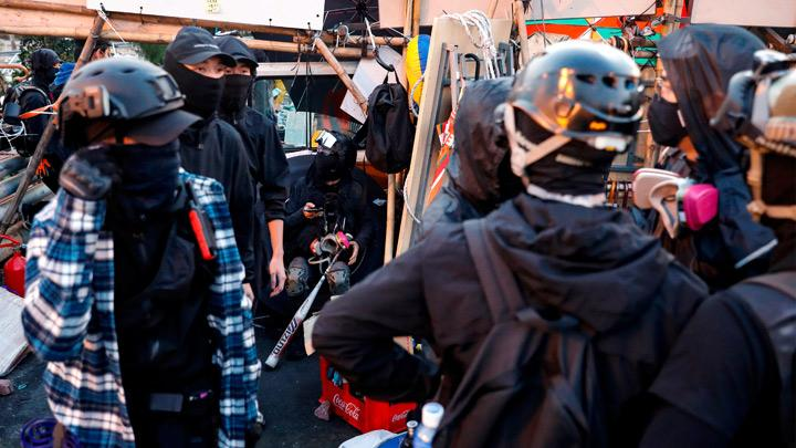 Anti-government protesters scout at a makeshift gate during a standoff with riot police at the Chinese University of Hong Kong, Hong Kong, China November 14, 2019. Earlier in the day, about 1,000 protesters blocked roads in the Central district at lunchtime. Wearing now-banned face masks and dressed in office wear, they marched and hurled bricks on to roads lined with some of the world's most expensive real estate and luxury flagship stores. REUTERS/Tyrone Siu