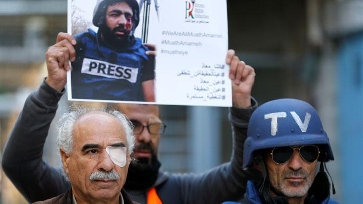 A demonstrator has his eye covered with a patch during a protest to show solidarity with Palestinian journalist Muath Amarna, who was shot in his eye, in Hebron in the Israeli-occupied West Bank November 18, 2019. REUTERS/Mussa Qawasma