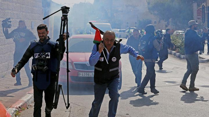 Palestinian journalists react to a stun grenade fired by Israeli forces during a protest to show solidarity with their colleague Muath Amarna, who was shot in his eye, in Bethlehem in the Israeli-occupied West Bank November 17, 2019. REUTERS/Mussa Qawasma