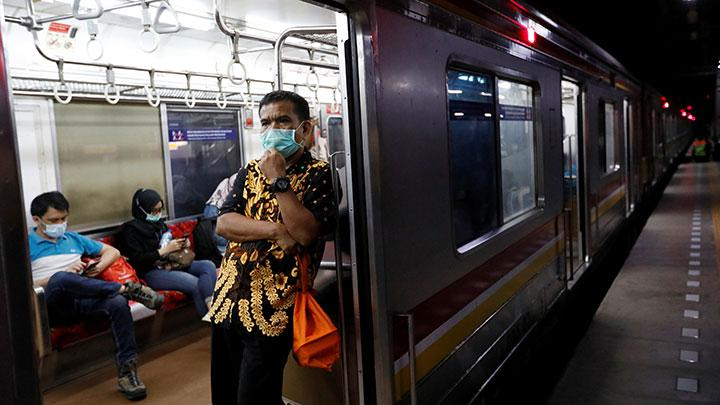 Man wearing a protective mask stands inside a commuter train during the imposition of large-scale restrictions by the government to prevent the spread of coronavirus disease (COVID-19) in Jakarta, Indonesia, April 21, 2020. The governor of Indonesia's capital Jakarta said on Wednesday he would extend large-scale social restrictions for an additional month to May 22 and also ensure residents prayed at home during the Muslim fasting month of Ramadan to curb the spread of the coronavirus. REUTERS/Willy Kurniawan