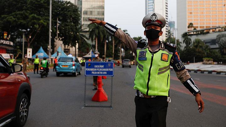 A police officer gestures while checking the motorists as the government imposed large-scale restrictions to prevent the spread of the coronavirus disease (COVID-19) in Jakarta, Indonesia, April 20, 2020.