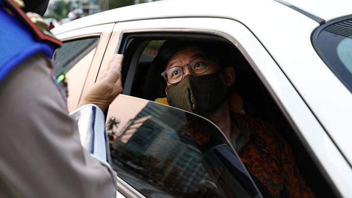 A man wearing a protective face mask looks on through a window of a car while being checked by a police officer as the government imposed large-scale restrictions to prevent the spread of the coronavirus disease (COVID-19) in Jakarta, Indonesia, April 20, 2020. While Jakarta has not imposed a full lock-down, Baswedan said he would increase enforcement of the restrictions in place which include limiting public gatherings. REUTERS/Willy Kurniawan