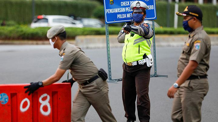 A police officer holds a sign while guarding at a check point as the government imposed large-scale restrictions to prevent the spread of the coronavirus disease (COVID-19) in Jakarta, Indonesia, April 20, 2020. The governor of Indonesia's capital Jakarta said on Wednesday he would extend large-scale social restrictions for an additional month to May 22 and also ensure residents prayed at home during the Muslim fasting month of Ramadan to curb the spread of the coronavirus. REUTERS/Willy Kurniawan