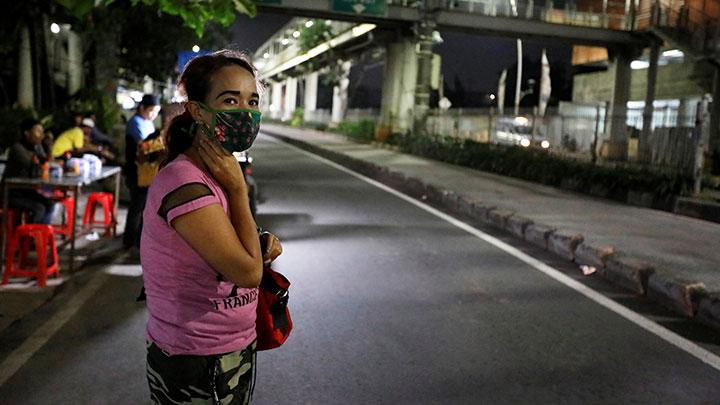 Woman wearing a protective mask stands on the sidewalk as she waits for a public minivan during the imposition of large-scale restrictions by the government to prevent the spread of coronavirus disease (COVID-19) in Jakarta, Indonesia, April 21, 2020.