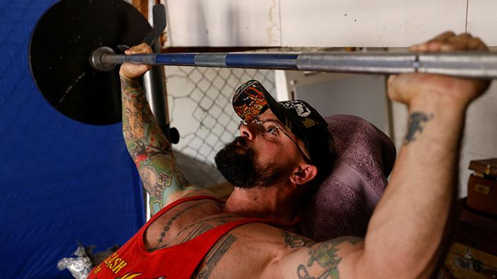 Paulo Batista, a transgender man who is training to enlist in the U.S. military despite the Trump administration's ban on transgender people, works out in his garage in San Diego, California, U.S., October 1, 2020. Batista is transgender, effectively banned from military service under a policy announced by U.S. President Donald Trump in 2017 and formally adopted in 2019.  REUTERS/ Mike Blake