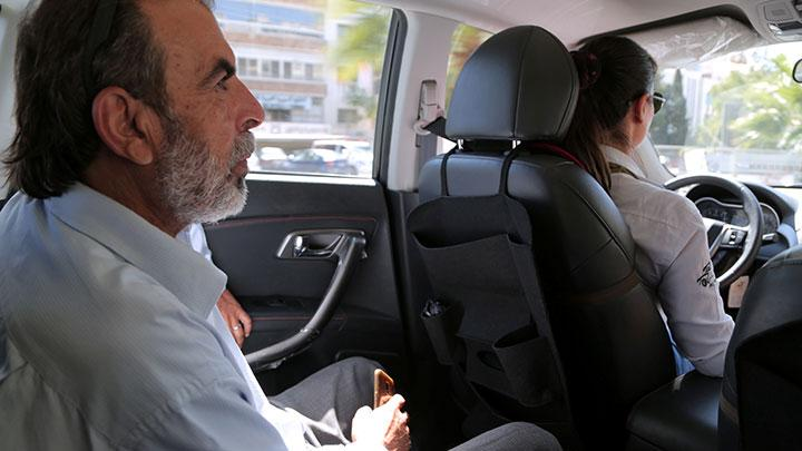 Kinana al-Bunni, 37, a female taxi driver, takes a passenger in Damascus, Syria October 2, 2020. REUTERS/Yamam Al Shaar