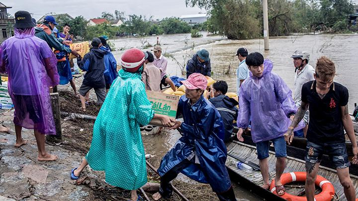 Penduduk lokal dan relawan mengirimkan paket bantuan kepada penduduk yang terkena dampak banjir besar di Quang An Commune, Thua Thien Hue, Vietnam, 20 Oktober 2020. Yen Duong/International Federation of the Red Cross (IFRC)/Handout via REUTERS