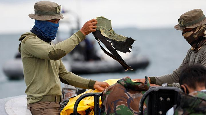 A member of the Indonesian navy holds a piece of debris, that was found at the sea, during search and rescue operation for the Sriwijaya Air flight SJ 182, at the sea off the Jakarta coast, January 12, 2021. REUTERS/Willy Kurniawan