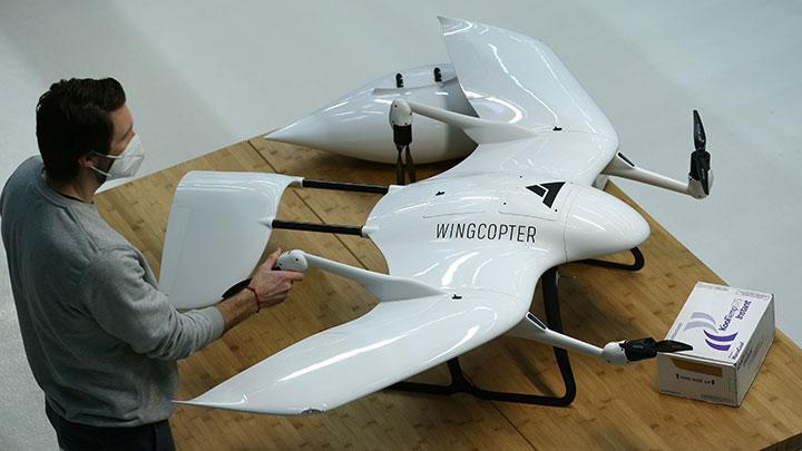 An employee of German start-up company Wingcopter stands next to a drone, designed for distribution of medical products, as well as COVID-19 vaccines, as the spread of COVID-19 continues, in Weiterstadt near Darmstadt, Germany, February 2, 2021. Wingcopter is one of several drone start-ups seeking to play a role in the delivery of vaccines in regions lacking good storage facilities or developed transport infrastructure. REUTERS/Ralph Orlowski